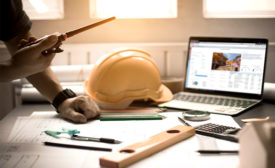 desk with hard hat and computer