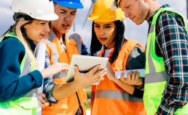Construction workers looking at a tablet