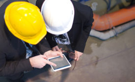 men in construction hard hats looking at a tablet