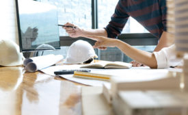 hands and hard hat on a desk