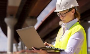 Female engineer with laptop at construction site