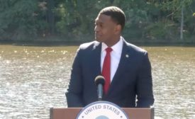 EPA administrator stands at an outdoor podium with water flowing in the background