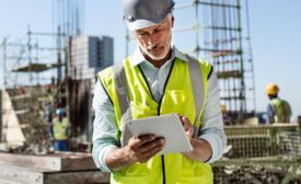 a man in a yellow construction vest looking at a tablet