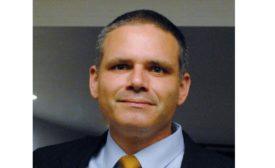Headshot of Matthew Tejada wearing suit jacket, light blue shirt and gold tie