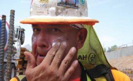 Construction tradesworker applies sunscreen