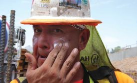Construction tradesworker applies sunscreen