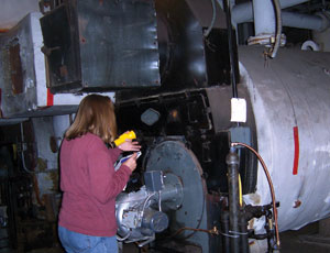 Community Environmental Center technician checks a boiler during an energy audit of a multifamily building.