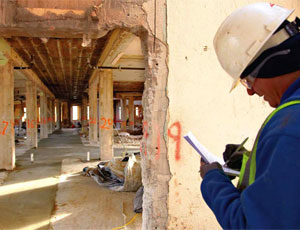 Carlos Romero takes measurements to see if the header needs to be cut on this first-floor hallway. The former hospital's 8-ft-wide corridors will remain intact and will be incorporated into the new design.