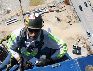 Hanging from a protective harness, Hague uses a dial gauge to check for excessive play in the crane's rotator gear.