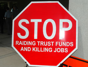 "This ""road sign"" conveyed FTBA's stance on raiding road funds to balance the state budget."