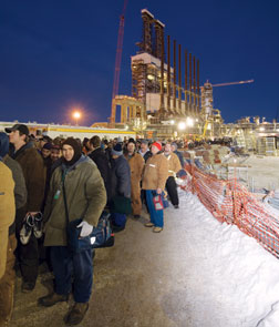 Workers queue up after day of construction. The median age of construction workers in the oil-sands region is 50 years.
