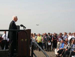 Jerry Roper, chief executive of the Chicagoland Chamber of Commerce, welcomes guests during a commissioning ceremony while a plane approaches new Runway 10L/28R.