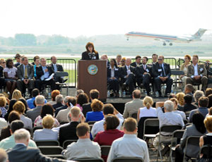 Rosemarie Andolino, executive director of the O'Hare Modernization Program, welcomes guests to the commissioning of a runway extension just as a jet lands. Chicago Mayor Richard Daley is to her right.