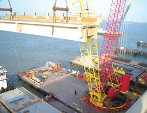 Traylor Bros. crawler cranes mounted on barges take a beating in the humid salt-air environment.