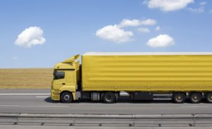 Blue sky over yellow truck on a highway (1)