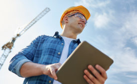 construction worker w/tablet, crane in background