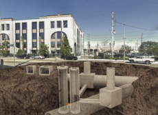 Pipes in the ground shown with building in the background